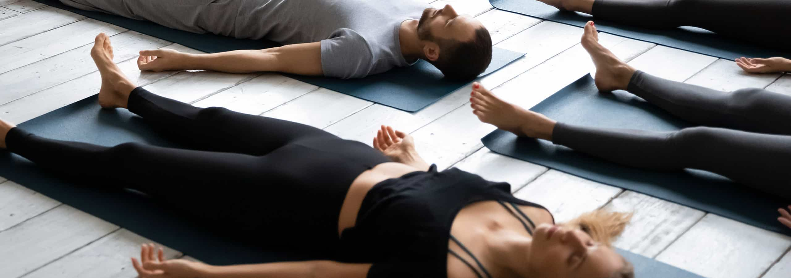 People laying on the ground during a yoga class